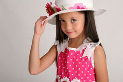 Tip of my hat. Young girl in spring outfit, including white hat and pink dress Royalty Free Stock Photo