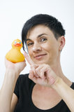 Tip on the rubber duck. Head-and-shoulder view of a black-haired woman against white background with yellow rubberduck in the Hand; cream swab on the nose of Royalty Free Stock Image