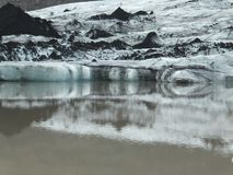 Tip of Sólheimajökull glacier in south of Iceland, its beautiful structure reflected in water stock image