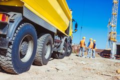 Tip truck and construction workers. Three builders in uniform standing near a big yellow tip truck at construction site royalty free stock images