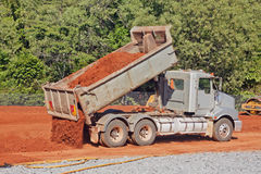 Tip truck dumping dirt on a construction site Royalty Free Stock Photos
