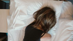 Tip view of depressed young woman lying face down on the bed. Crying girl shaking head and pulling at hair with anger. stock video footage
