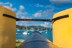 Tip of a vintage cannon through the turret facing the sailboats. In the Caribbean Stock Photography