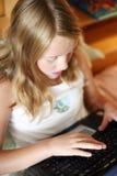 Tipe biondo della ragazza sul computer portatile Fotografia Stock Libera da Diritti