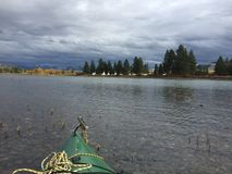Tipi Camp along the River. Native American Tipis in a camp along a river in Montana seen from a kayak on the other shore Stock Image