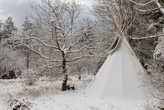A tipi covered in snow in winter. A snowy winter landscape with a tipi tent royalty free stock photo
