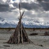 Tipi d'Alaska construit dans un lit de la rivière sec avec les montagnes majestueuses comme contexte photos libres de droits