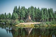 Tipi des amerikanischen Ureinwohners, der im See sich reflektiert lizenzfreie stockbilder