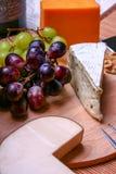 3 tipi di formaggio, di roquefort di natura morta, di cheddar, di formaggio affumicato e di noci rosse e verdi dell'uva Fotografia Stock