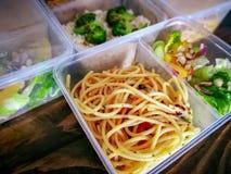 Tipi differenti di alimenti asportabili in contenitori microwavable su un fondo di legno fotografie stock