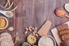 Tipi differenti di alti alimenti del carboidrato sui precedenti di legno fotografie stock