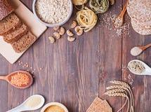 Tipi differenti di alti alimenti del carboidrato sui precedenti di legno fotografia stock