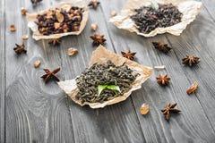 Tipi differenti di foglie di tè asciutte su fondo di legno fotografia stock libera da diritti