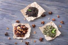 Tipi differenti di foglie di tè asciutte su fondo di legno fotografie stock libere da diritti