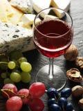 Tipi differenti di formaggi con il vetro ed i frutti di vino Immagine Stock