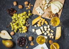 Tipi differenti di formaggi vetri a bordo, dell'oliva, di frutti, della mandorla e di vino sulla tavola di pietra nera immagini stock
