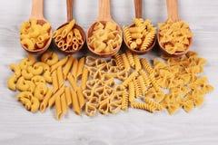 Tipi differenti di paste che si trovano in cucchiai di legno Fotografia Stock