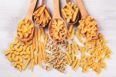 Tipi differenti di paste che si trovano in cucchiai di legno Fotografie Stock