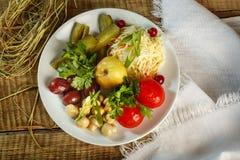 Tipi differenti di verdure sul piatto bianco I cetrioli marinati, la ciliegia del pomodoro, i verdi, bacche, mele al forno sono s Fotografie Stock