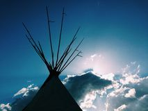 Tipi. Silhouette sky evening sun beam clouds camping outside no one nobody copy space Royalty Free Stock Image