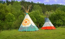 TIPI(teepee). A small group of four teepees forms a small camp in a meadow surrounded by forest. Teepees were traditional housing for Native Americans in Great Stock Photography