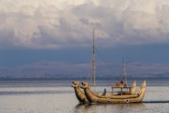 Tipical totora made boat in Titicaca lake. Island of Sun in Bolivia with clouds in the sky Stock Images