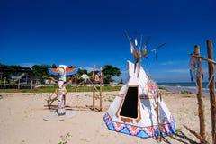 Tipin och totempålen för indian slösar den indiska på stranden sk Fotografering för Bildbyråer