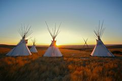 Tipis at sunrise on the prairie. Group of North American Plains Indian style tipis at sunrise on the prairie stock photos