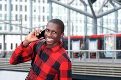 Tipo africano allegro che per mezzo del telefono cellulare alla stazione ferroviaria Fotografia Stock