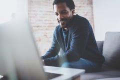 Tipo africano barbuto allegro che lavora al computer portatile mentre sedendosi sofà al suo posto moderno dell'ufficio Concetto d Fotografia Stock Libera da Diritti