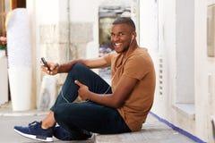 Tipo africano che si siede all'aperto con il telefono cellulare Immagini Stock