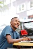 Tipo africano felice che si siede ad un caffè Immagini Stock Libere da Diritti
