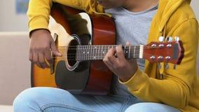 Tipo afroamericano che impara come giocare chitarra acustica, istruzione musicale archivi video