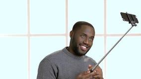 Tipo afroamericano divertente che prende selfie con il monopiede archivi video
