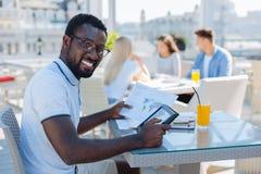 Tipo afroamericano emozionante che studia al caffè Fotografie Stock Libere da Diritti