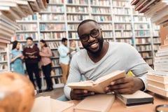 Tipo afroamericano etnico circondato dai libri in biblioteca Lo studente è libro di lettura fotografie stock