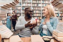 Tipo afroamericano etnico e ragazza bianca circondati dai libri in biblioteca Gli studenti stanno dando il regalo immagine stock libera da diritti