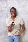 Tipo afroamericano sorridente con il telefono cellulare Immagini Stock