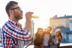 Tipo allegro che gode della bevanda dell'alcool sul terrazzo del tetto Immagini Stock Libere da Diritti