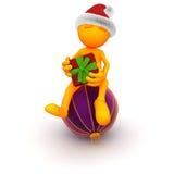 Tipo arancio: Sedendosi su un ornamento di Natale con il presente Fotografia Stock Libera da Diritti