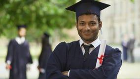 Tipo in armi dell'incrocio dell'attrezzatura di graduazione con il diploma a disposizione, risultato sorridente archivi video