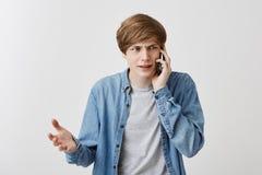 Tipo arrabbiato nervoso con l'espressione seria, avendo conversazione telefonica, fronte aggrottante le sopracciglia, gesturing a Immagini Stock