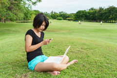 Tipo asiático de la muchacha un poco de texto en su teléfono móvil Foto de archivo