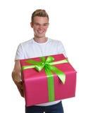 Tipo attraente che mostra il suo regalo di natale Immagine Stock
