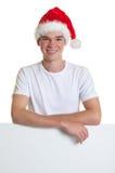 Tipo attraente con il cappello di natale su un segno in bianco Immagini Stock Libere da Diritti