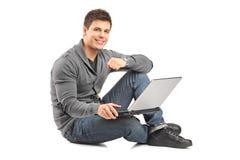 Tipo bello che lavora ad un computer portatile e che si siede su un pavimento Fotografie Stock