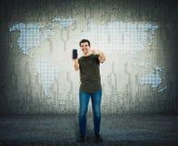 Tipo bello che presenta uno smartphone d'avanguardia Uomo sorridente positivo che mostra un nuovo telefono sopra fondo moderno as fotografia stock libera da diritti