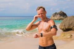 Tipo bello che ripara i suoi earbuds e che si prepara per l'allenamento sulla spiaggia Fotografie Stock