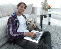 Tipo bello con il computer portatile che abbraccia il suo cane e che si siede vicino allo strato Immagini Stock