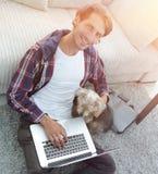 Tipo bello con il computer portatile che abbraccia il suo cane e che si siede vicino allo strato Fotografie Stock Libere da Diritti